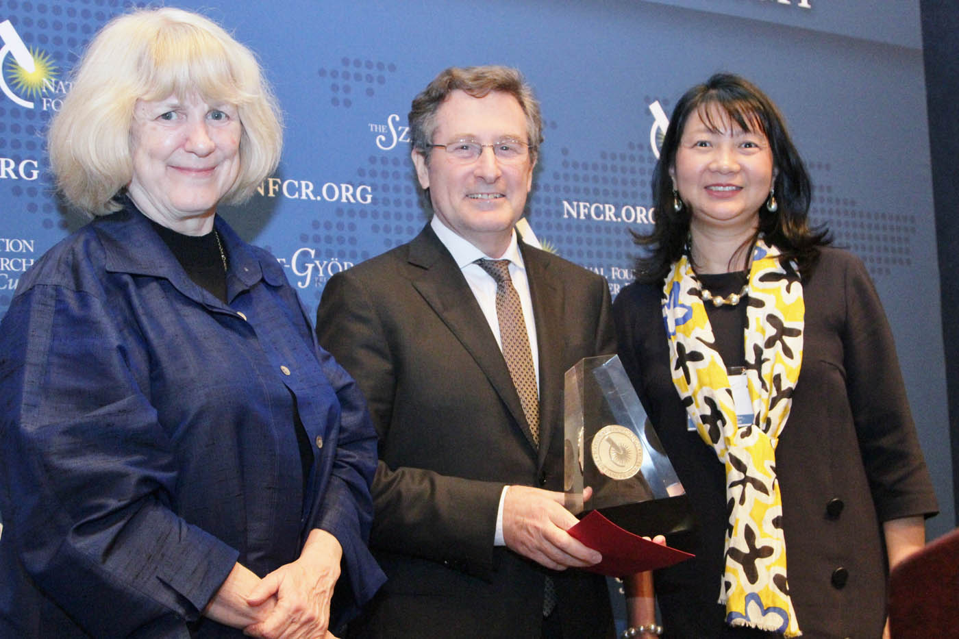 Dr. Michael Hall receiving award from last year's winner, Dr. Mary-Claire King, and Dr. Sujuan Ba from NFCR