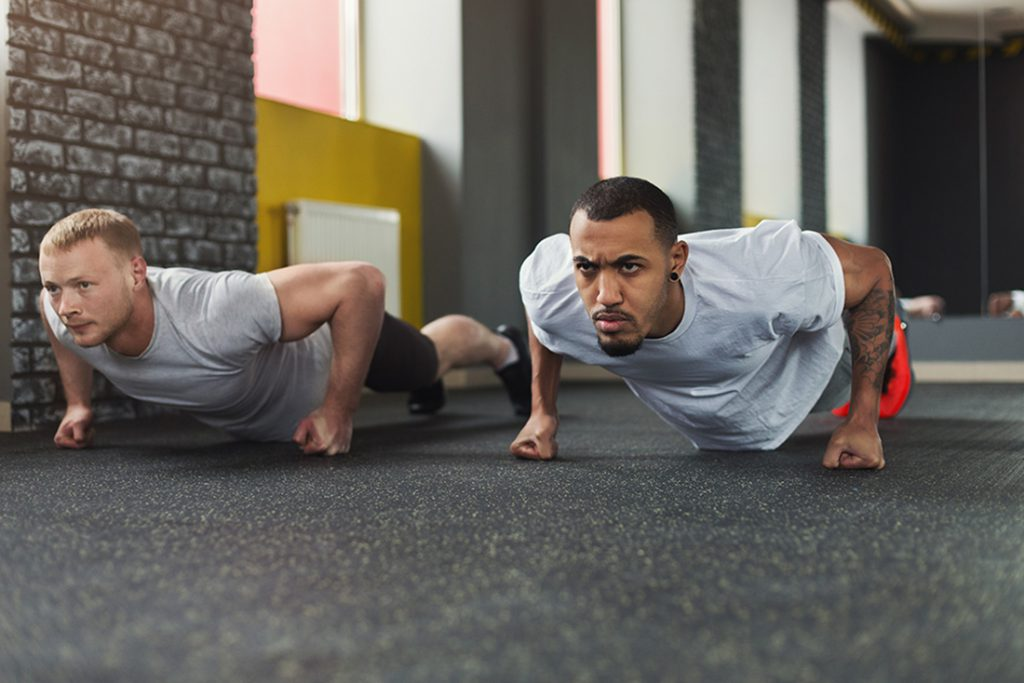 Two men do push-ups on their knuckles with extreme focus