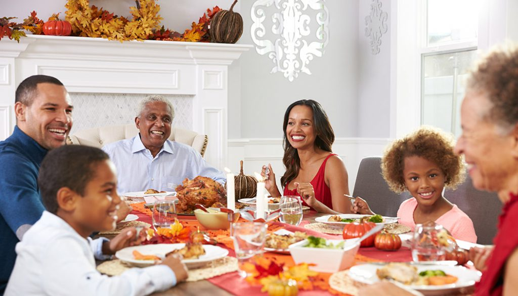 Three generations of family sit at table for Thanksgiving Dinner