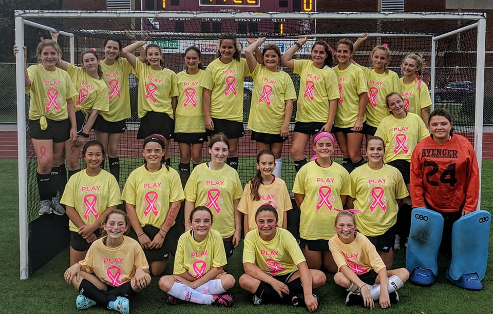 East Greenwich High School Field Hockey together wearing yellow shirts with pink ribbons