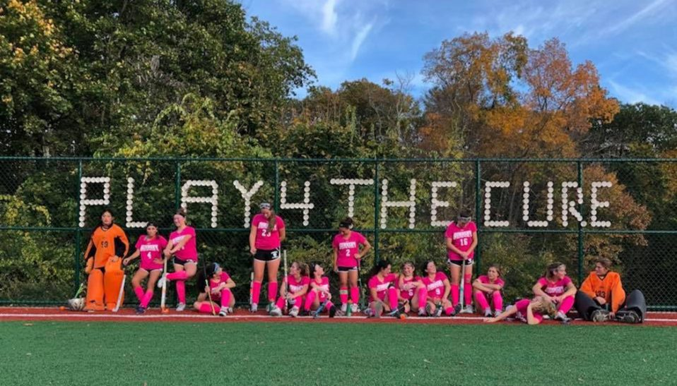 The Gunnery School Field Hockey pose in pink in front of the fence they put cups in to spell out Play4TheCure